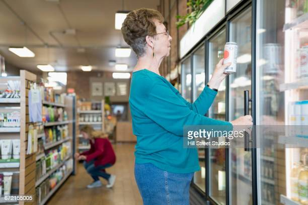 Woman examining can from freezer case in nutrition store