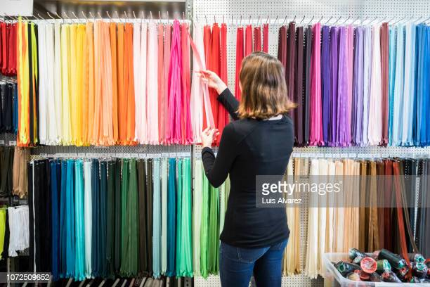 woman examining colorful zippers on rack in store - textile industry stock pictures, royalty-free photos & images