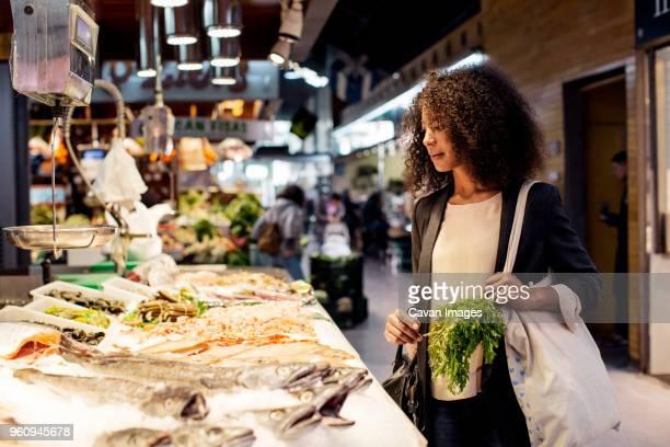 woman examining fish in market - vis stockfoto's en -beelden