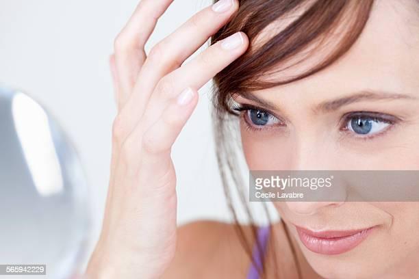 Woman examining hair in the mirror