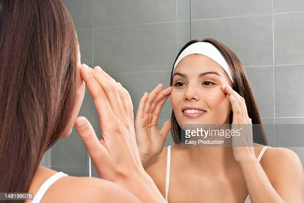 woman examining her face in mirror - massage rooms photos et images de collection