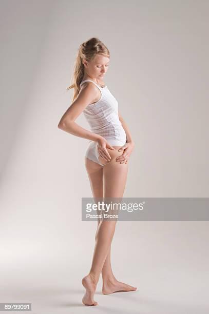 woman examining her skin - celulite imagens e fotografias de stock