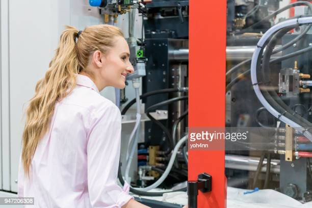 woman examining industrial lathe - mechatronics stock pictures, royalty-free photos & images