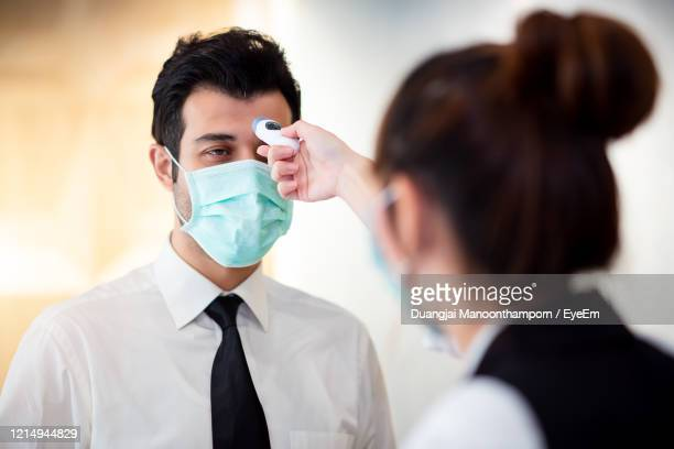 woman examining man with equipment for coronavirus - examining stock pictures, royalty-free photos & images