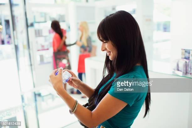 Woman examining perfume in drugstore