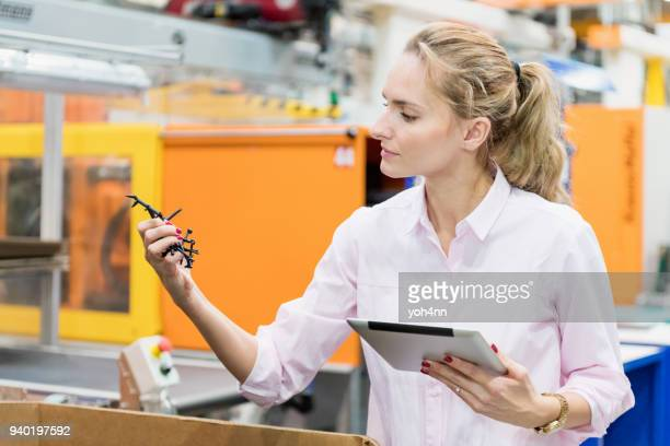 Woman examining quality of plastic product