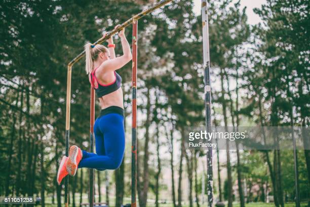 woman exercise in the park - chin ups stock photos and pictures