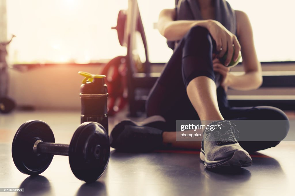 Woman exercise workout in gym fitness breaking relax holding apple fruit after training sport with dumbbell and protein shake bottle healthy lifestyle bodybuilding. : Stock Photo