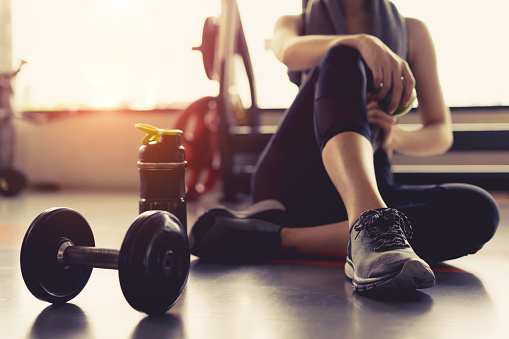 Woman exercise workout in gym fitness breaking relax holding apple fruit after training sport with dumbbell and protein shake bottle healthy lifestyle bodybuilding. 871070868