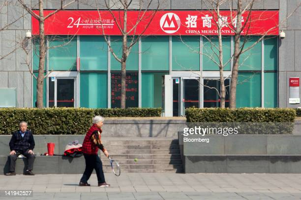 A woman exercises in front of a China Merchants Bank Co Ltd branch in Beijing China on Tuesday March 27 2012 China Merchants Bank is expected to...