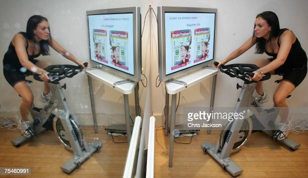 A woman exercises in front of a screen displaying puzzles and games as part of a full mind and body workout at the Fit Rooms on July 18 2007 in...