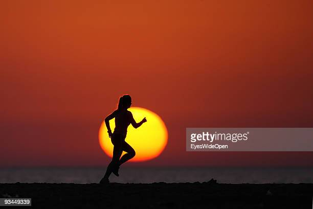 A woman Exercises on the beach at Sunset on July 16 2009 in Rhodes Greece Rhodes is the largest of the Greek Dodecanes Islands