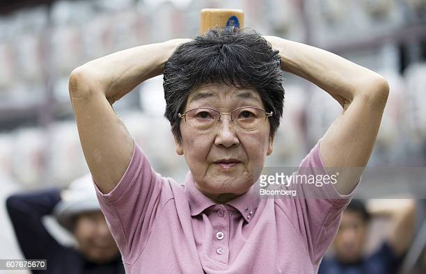 A woman exercises with a wooden dumbbell during an event marking Respect for the Aged Day at a temple in the Sugamo district of Tokyo Japan on Monday...