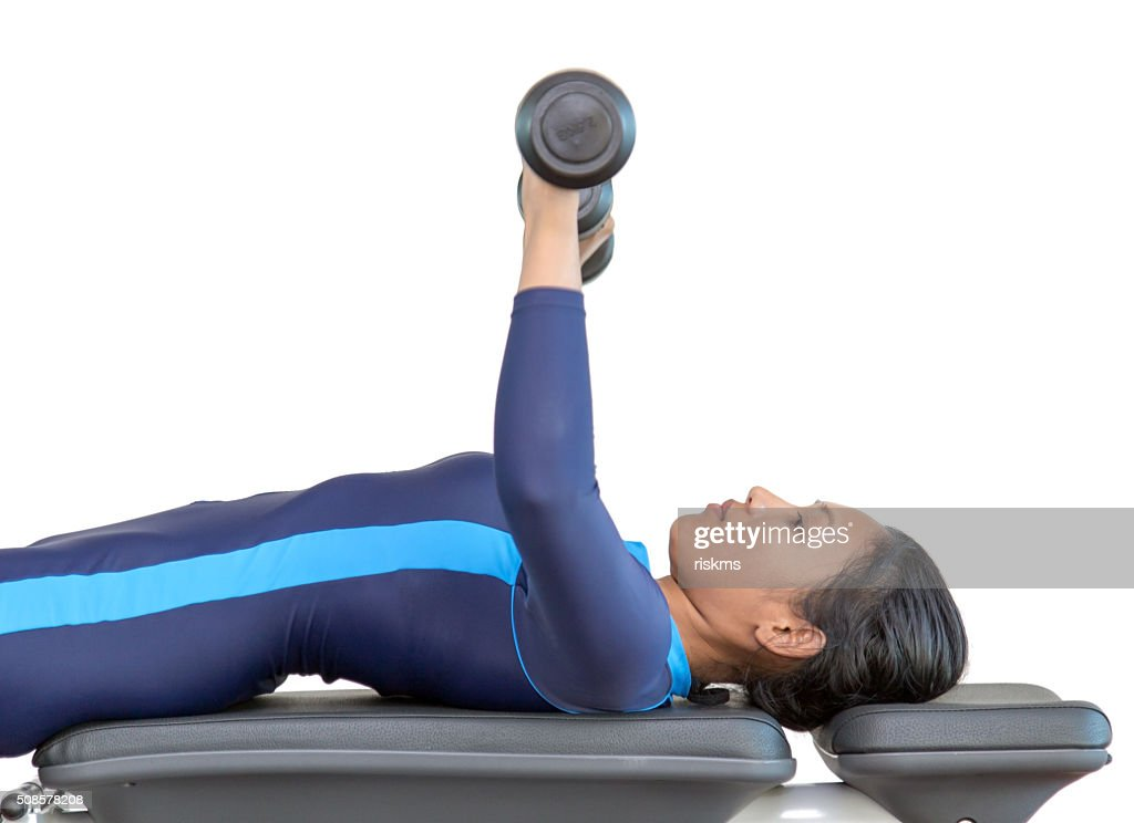 Woman exercises with dumbbells in the gym : Stockfoto