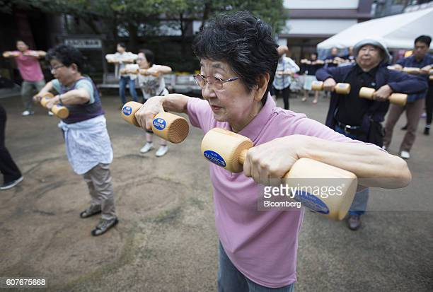 A woman exercises with wooden dumbbells during an event marking Respect for the Aged Day at a temple in the Sugamo district of Tokyo Japan on Monday...