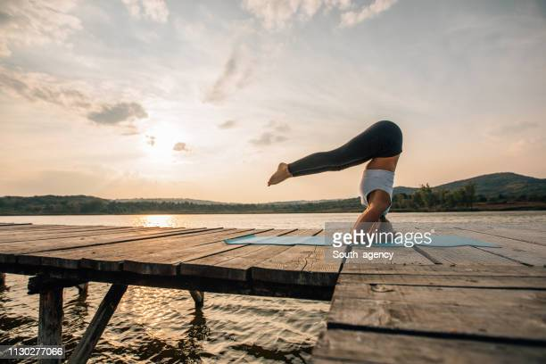 woman exercises yoga by the lake - yoga stock pictures, royalty-free photos & images