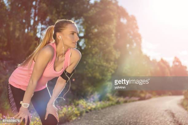 woman exercising and taking a break - forward athlete stock pictures, royalty-free photos & images