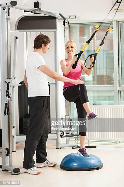 Mujer ejercicio y hablar con su profesor en un gimnasio.