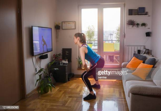 woman exercising and watching online fitness live streaming classes - small stock pictures, royalty-free photos & images