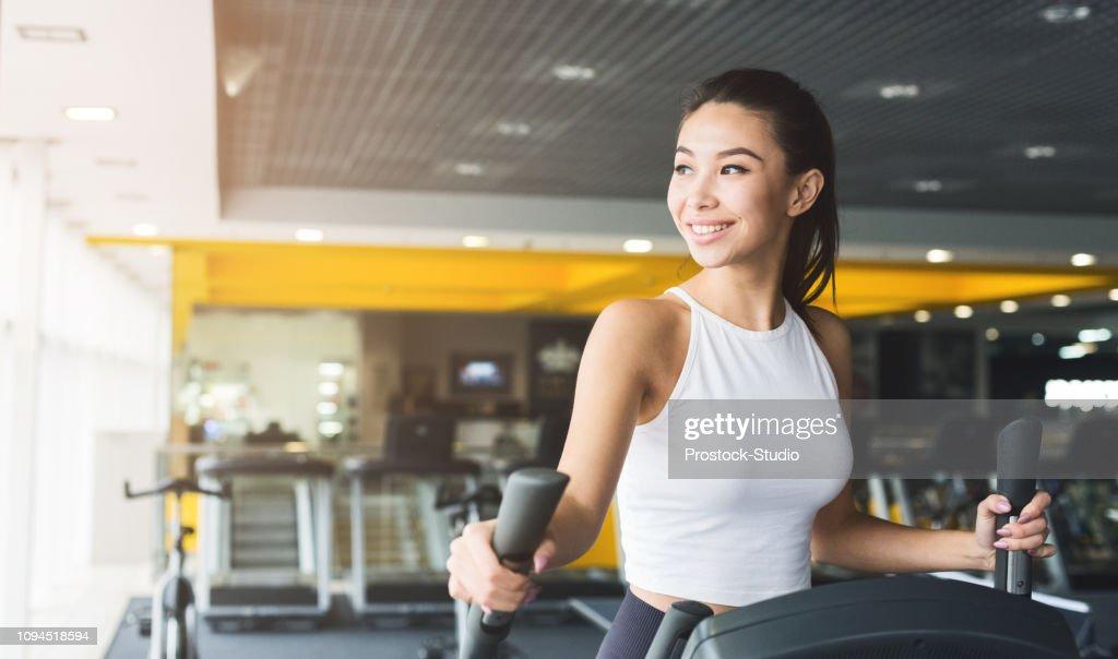 Frau im Crosstrainer im Fitness-Studio trainieren : Stock-Foto