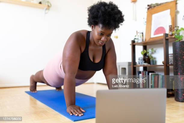 woman exercising at home following a fitness video online - push ups stock pictures, royalty-free photos & images