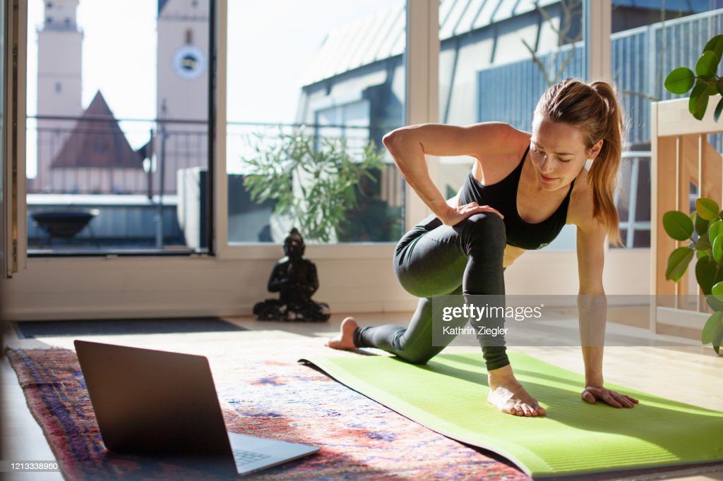 Woman exercising at home in front of her laptop, stretching her legs : Stockfoto