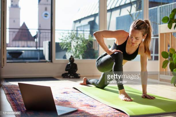 woman exercising at home in front of her laptop, stretching her legs - yoga stockfoto's en -beelden