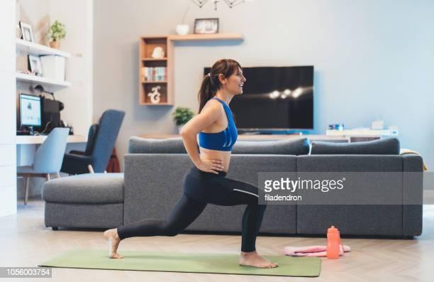 mulher exercitando em casa - flexionando perna - fotografias e filmes do acervo