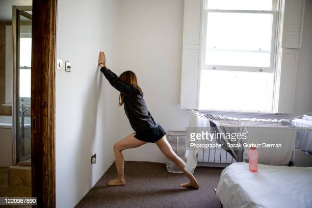 a woman exercising at home - stretching stock pictures, royalty-free photos & images