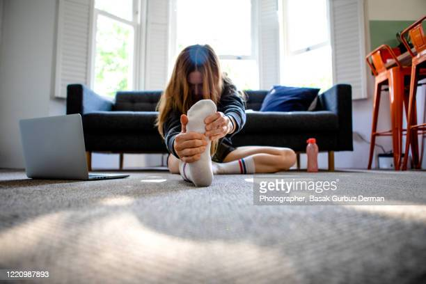 a woman exercising at home, watching exercise videos from ler laptop. - relaxation exercise stock pictures, royalty-free photos & images