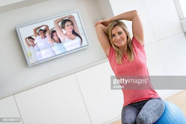 Woman exercising at home watching tv