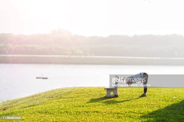 woman exercising at lakeshore - metthapaul stock photos and pictures