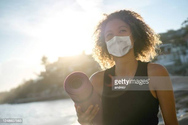 woman exercising at the beach wearing a facemask and holding a yoga mat - wellbeing stock pictures, royalty-free photos & images
