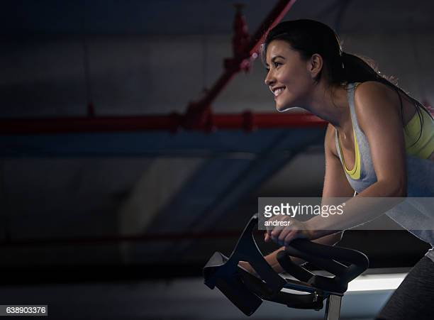 woman exercising at the gym - spinning stockfoto's en -beelden
