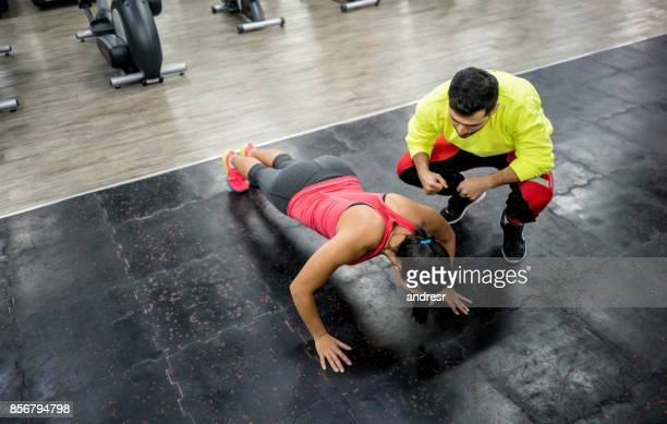 woman exercising at the gym with a personal trainer - coach stock pictures, royalty-free photos & images