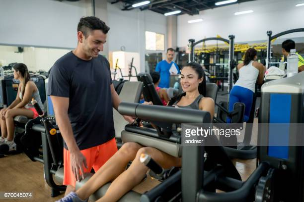 Woman exercising at the gym with her personal trainer
