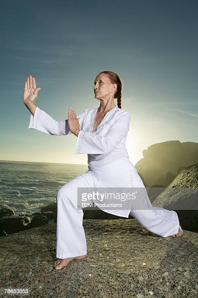 woman exercising by ocean - artes marciais imagens e fotografias de stock