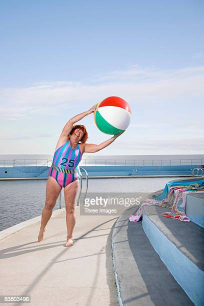 Woman exercising by the pool with a beach ball