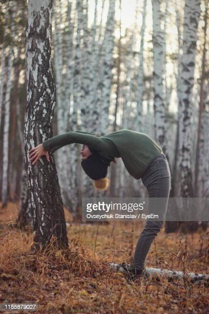 woman exercising by tree trunk in forest during winter - une seule jeune femme photos et images de collection
