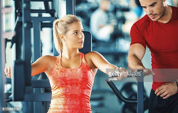 Woman exercising in a gym with an instructor.