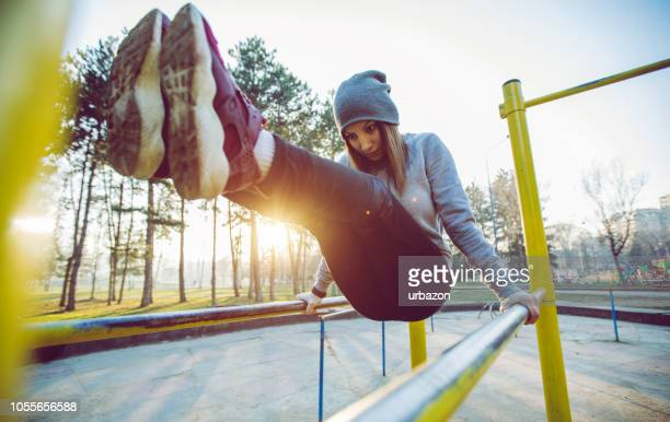 woman exercising in a public park - exercise equipment stock photos and pictures
