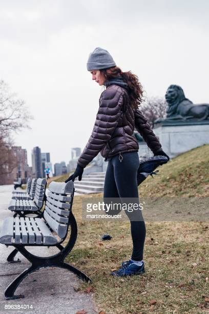 Woman exercising in city public park in winter.