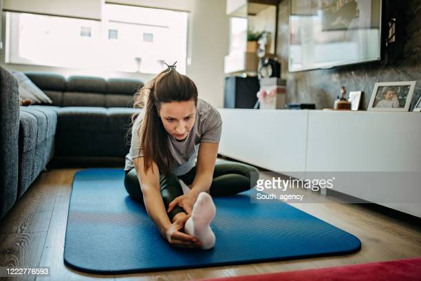 woman exercising in front of tv at home - in front of stock pictures, royalty-free photos & images
