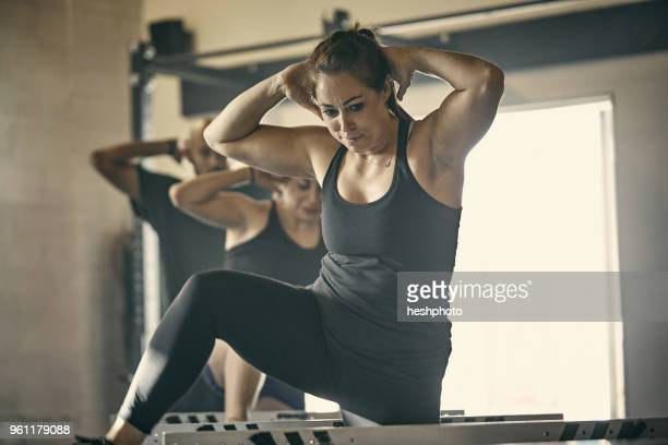 woman exercising in gym - heshphoto stock pictures, royalty-free photos & images