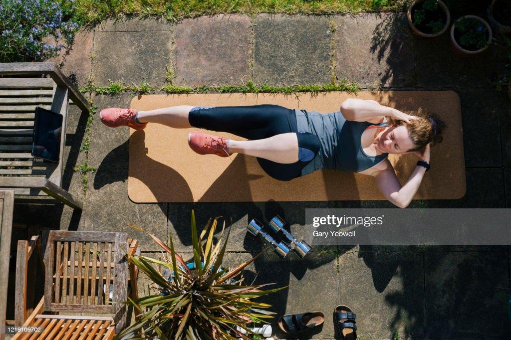 Woman exercising in her garden : Stock Photo