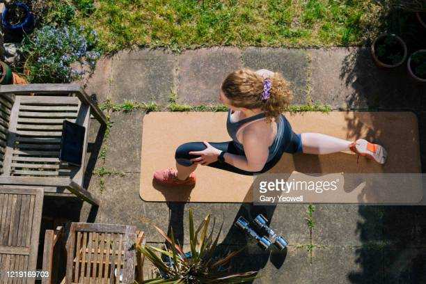 woman exercising in her garden - sports training stock pictures, royalty-free photos & images