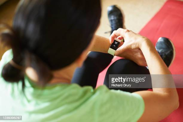 woman exercising in her living room - richard drury stock pictures, royalty-free photos & images