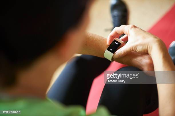 woman exercising in her living room - fitness tracker stock pictures, royalty-free photos & images