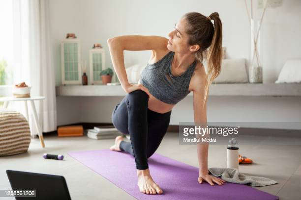 woman exercising in living room - mid adult women stock pictures, royalty-free photos & images