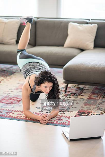 Woman exercising in the living room with laptop
